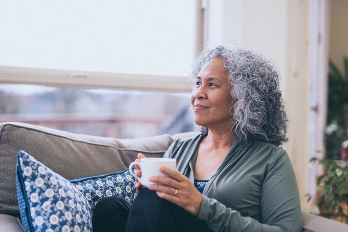 woman sitting on couch at home while holding a cup of coffee and looking out the window