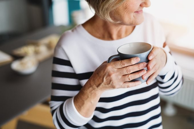 unrecognizable senior woman holding cup of coffee