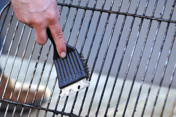 cleaning grill with wire brush close up
