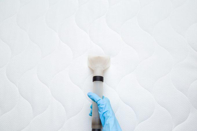 overhead shot of person vacuuming mattress