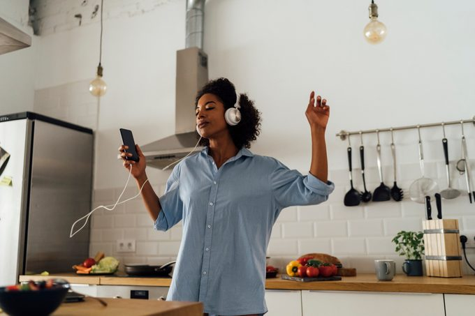 woman listening to music and dancing in kitchen at home