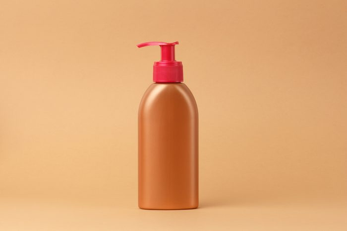 bronzing lotion bottle on beige background
