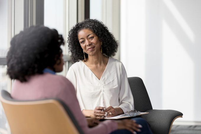 mature psychologist or therapist talking with patient