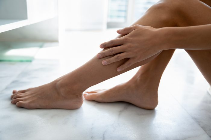 close up of woman touching her leg in bathroom