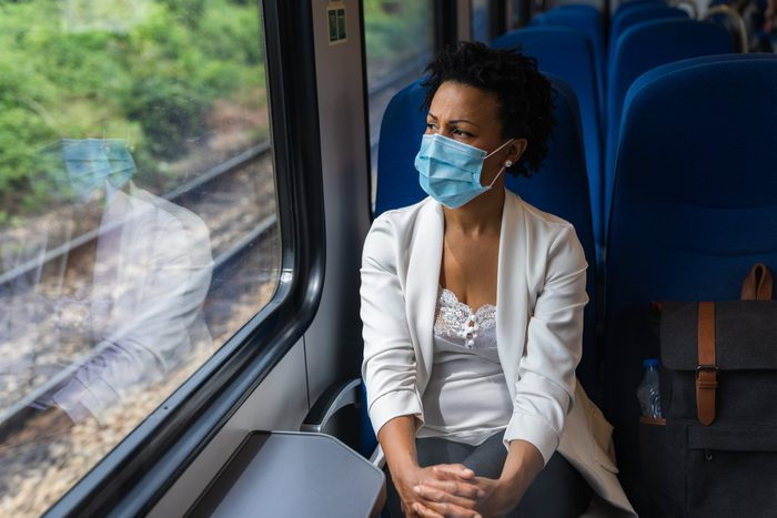 Business woman traveling with train while wearing a mask