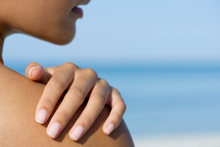 close up of woman touching her shoulder at the beach
