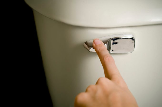 close up of finger on toilet flush
