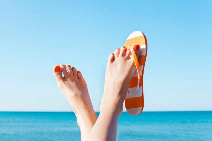 woman's feet at the beach with flip flops