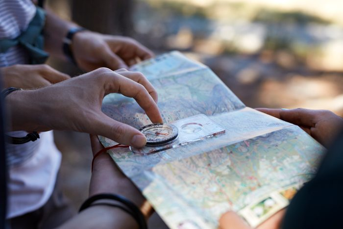 close up of hands holding compass up to map