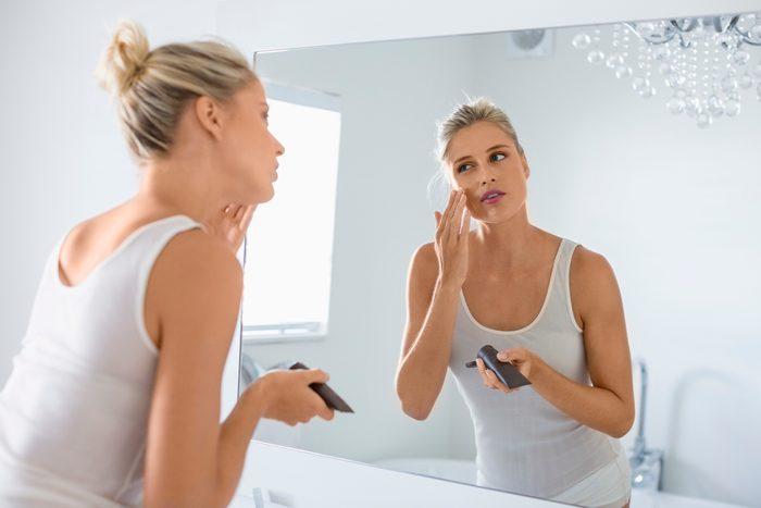 woman applying self tanner on face in bathroom