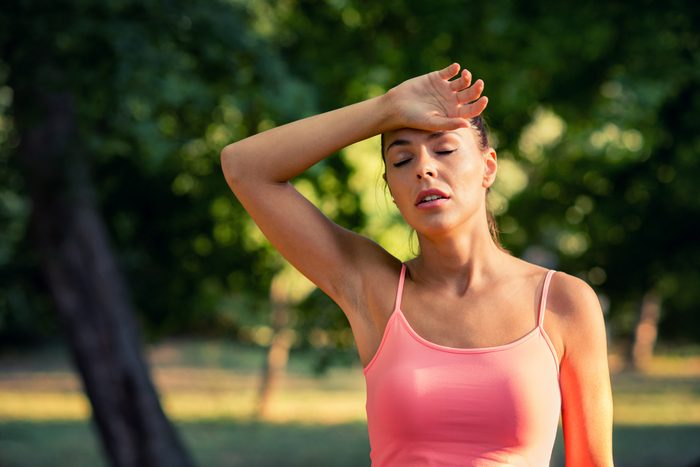 young woman sweating outside in the summer heat