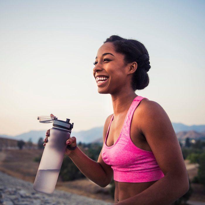 smiling female runner holding water bottle