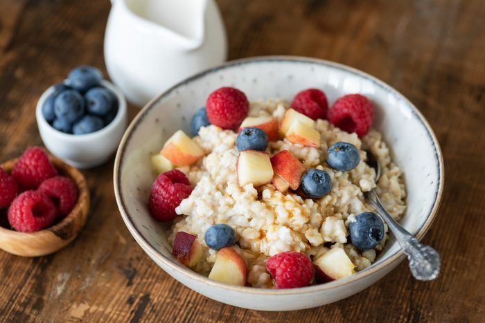 Oatmeal porridge with berries and honey on wooden table
