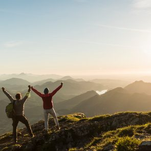 couple on top of mountain with hands up