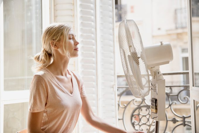 young woman sitting in front of fan at home