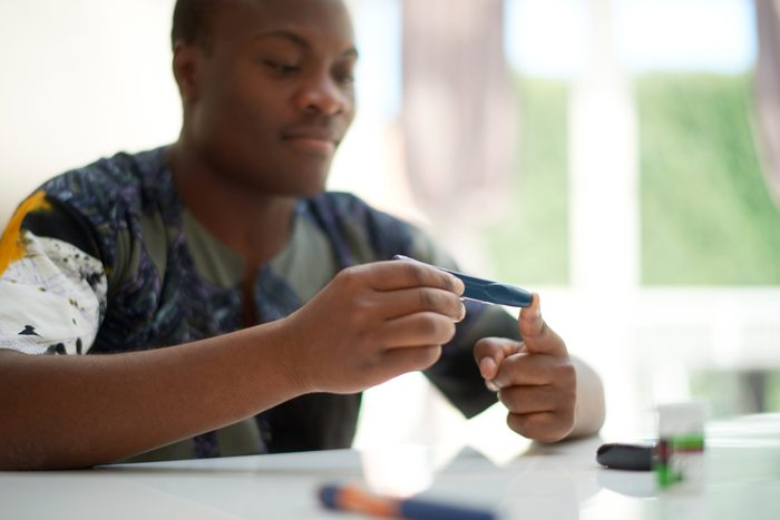 African American male using a blood sugar tester
