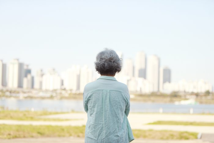 rear view of senior woman looking at view of city buildings