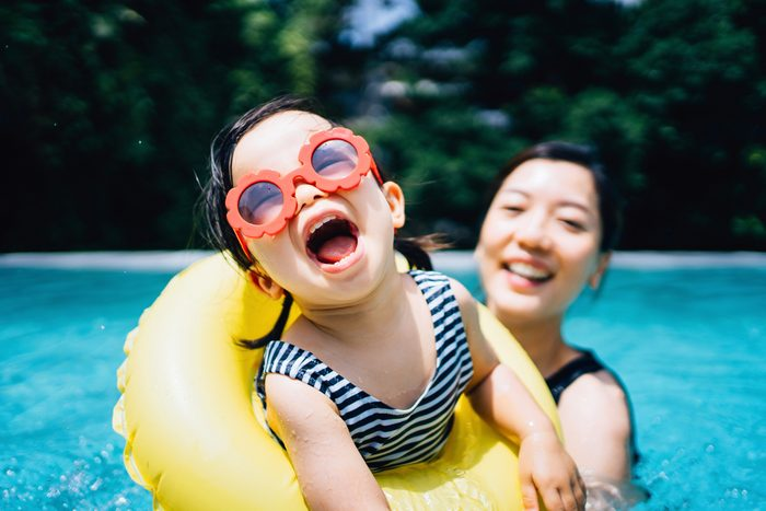 Happy toddler girl with sunglasses smiling joyfully and enjoying family bonding time with mother having fun in the swimming pool in summer