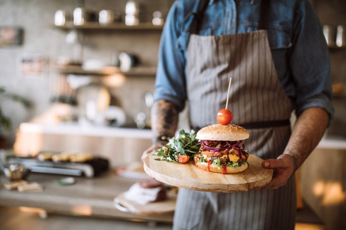 Man with apron standing in the kitchen and holding a wooden plate with prepared delicious hamburgers