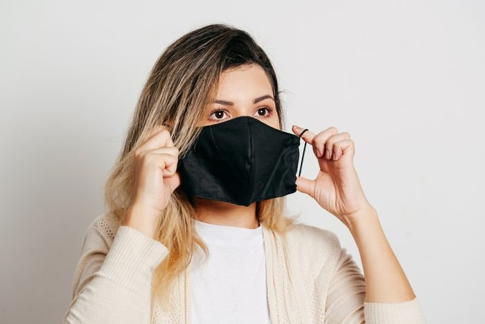 woman putting on protective face covering