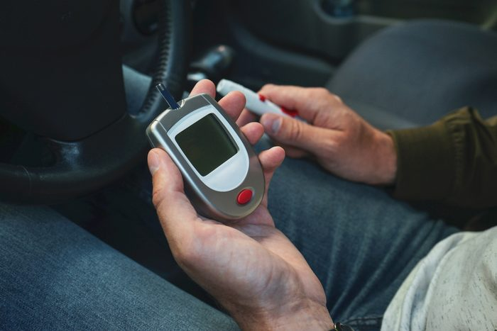 Glucometer and lancet pen in the hands of a man, close-up. Diabetes concept.