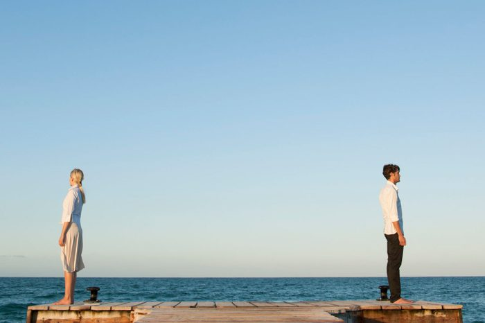couple standing back to back near ocean