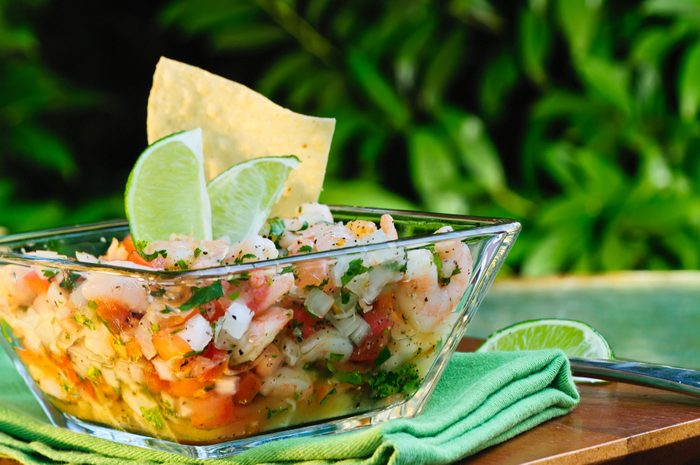 Ceviche in a bowl with lime on a wooden table