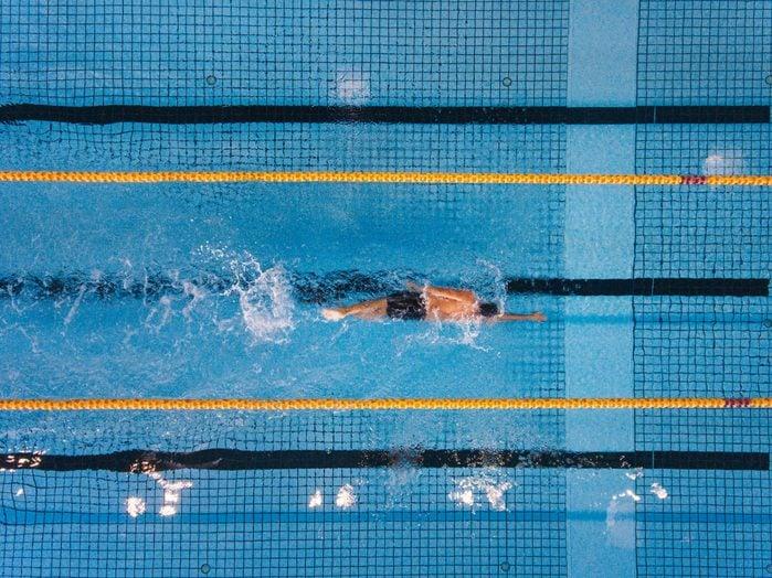 overhead shot of man swimming laps in pool