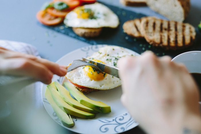 Breakfast with eggs, avocado, bread and tomatoes