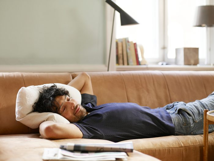 man laying on couch at home