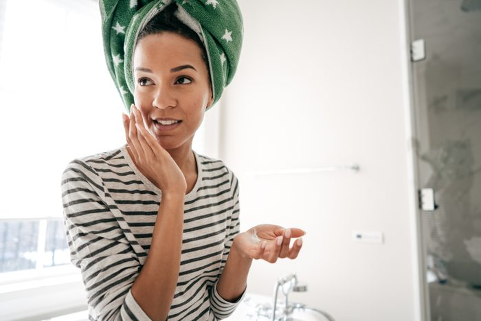 Woman with towel applying face cream