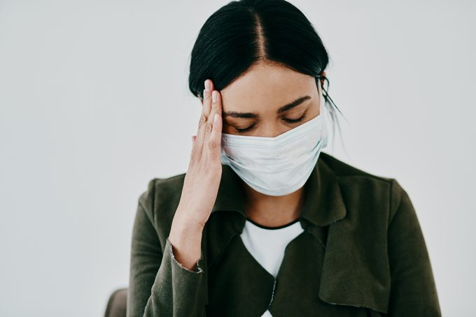 woman wearing a face covering and experiencing a headache