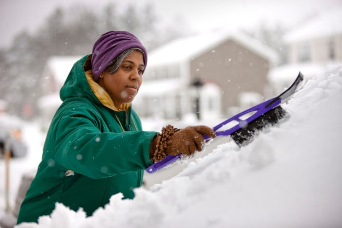 woman scraping snow from windshield