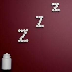 pill bottle and pills in zzz formation on dark red background