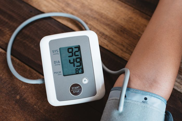 Cropped Hand Of Person With Blood Pressure Gauge On Wooden Table