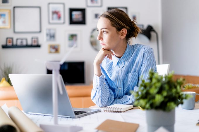 Woman in office looking sideways with wind turbine model on table