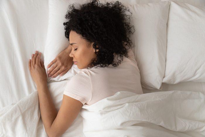 Healthy serene girl sleeping in comfortable bed, top view