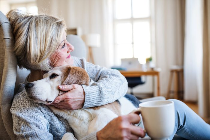 An active senior woman with a dog at home, resting.