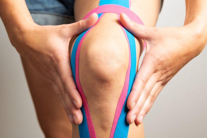 Female athlete with kinesio tape, muscle tape on knee
