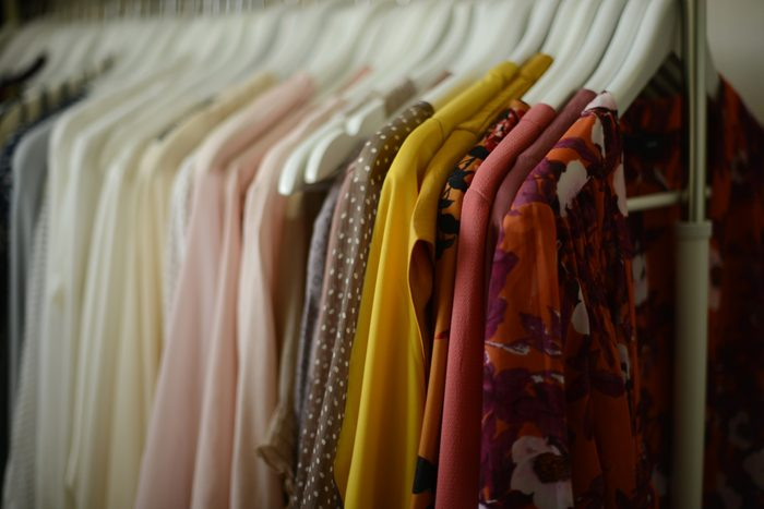 blouses arranged by color hanged on hangers in a row