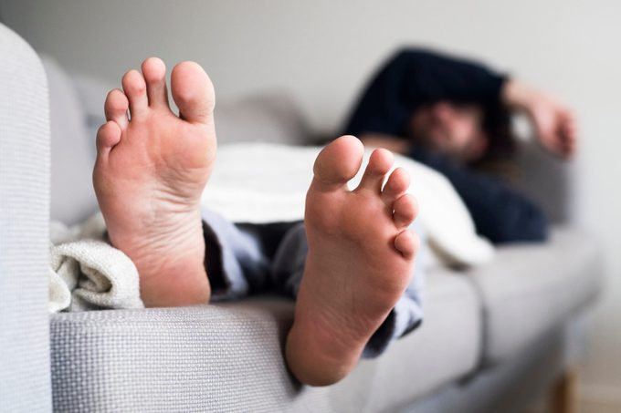 Man sleeping on sofa, close-up of feet