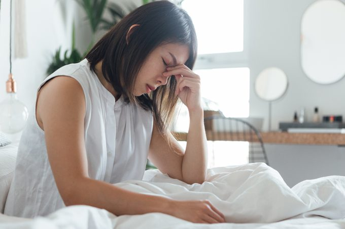 woman with headache sitting in bed