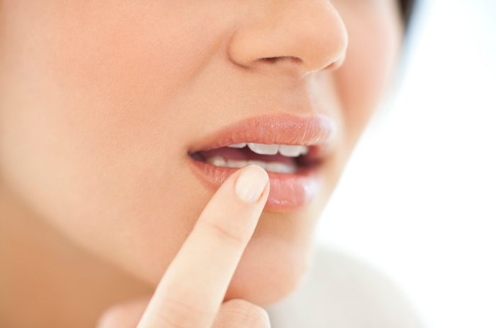 close up of woman with her finger on mouth area