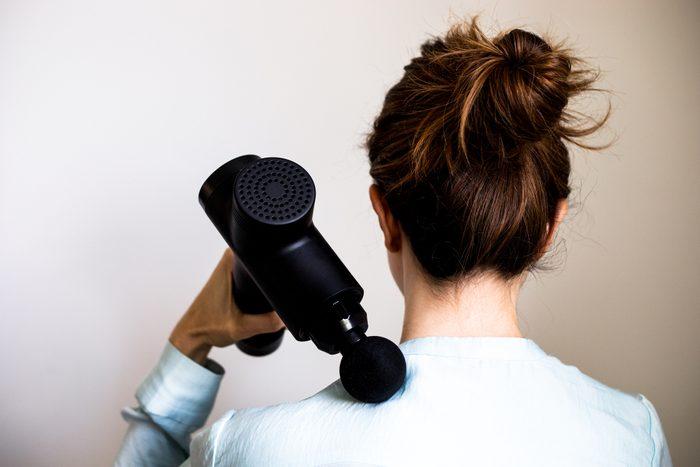 Rear view of a woman using massage gun / machine