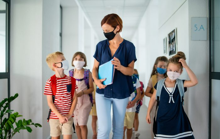 Teacher and children with face mask back to school after coronavirus quarantine.