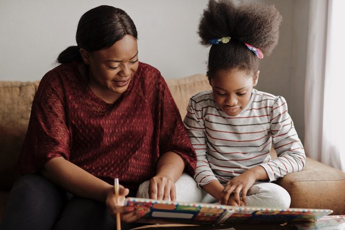 Mother and daughter reading a children's book on the couch