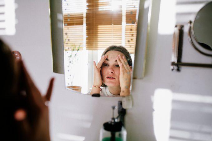 Woman looking in bathroom mirror