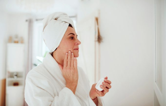 Mature woman in a bathroom at home applying moisturizer