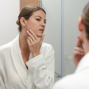 Woman in bathrobe looking in mirror at bathroom