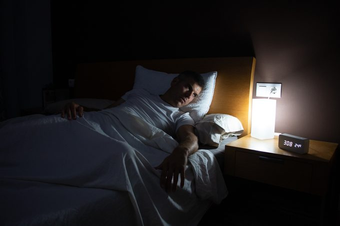 A man with insomnia looks at the clock in the middle of the night